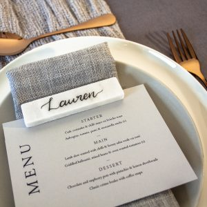 marble place setting with grey wedding menu sat on a plate with copper cutlery