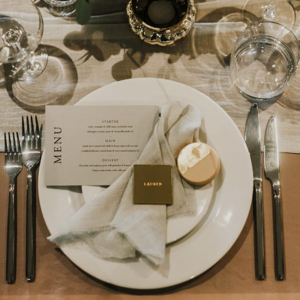 mirrored gold acrylic wedding place setting and favour sat on plate with napkin and menu