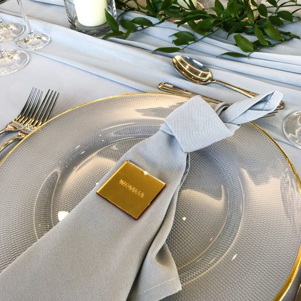 mirrored gold acrylic wedding place setting and favour sat on a clear charger plate with grey napkin